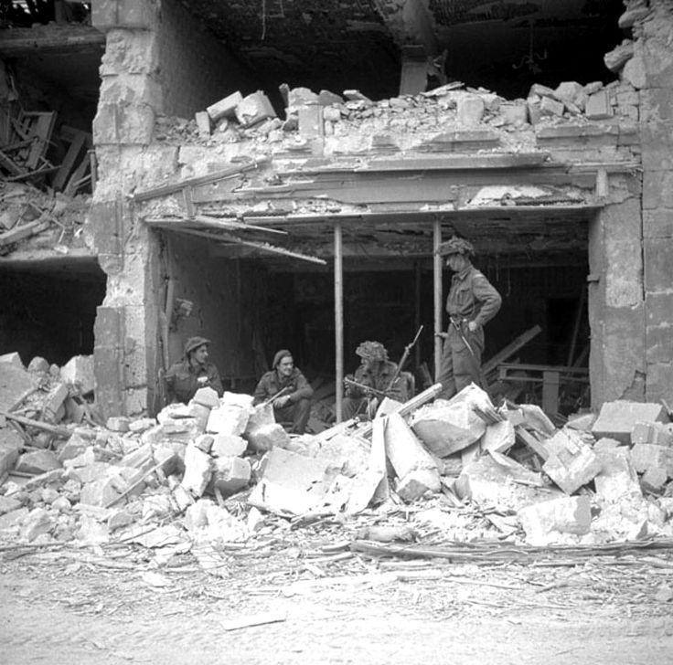 Canadian Infantrymen of the Regina Rifle Regiment (today known as the Royal Regina Rifles)rest inside a heavily damaged building during the Battle for Caen, part of Operation Overlord during the Battle of Normandy. Caen, Calvados, Lower Normandy, France. 10 July 1944. Image taken by Lt. Ken Bell.