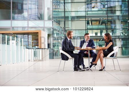 Three colleagues at a meeting in the foyer of a big business