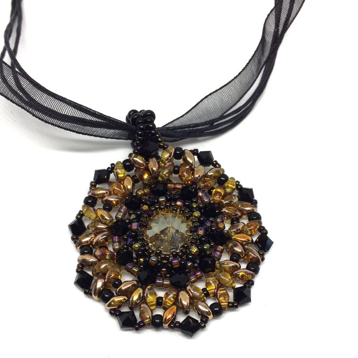 Alluring+Topaz+color+creates+an+elegant+necklace+design.+I+accented+the+Topaz+color+crystal+with+black+crystals+and+two+tone+gold+and+copper+glass+beads.+Around+the+edges+are+more+black+crystals.    The+loop+on+this+pendant+is+large,+so+you+can+take+it+off+the+ribbon+and+put+it+on+your+favorite+c...