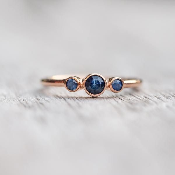 This three-stone sapphire engagement ring is classic yet eye catching. If you look very carefully you might spot a little heart in the center of the sapphire. Mesmerizing right?     The band is super dainty and the sapphires have been set with a low profile for comfortable everyday wear.