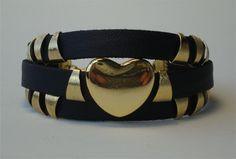 Bracelete em couro sintético preto com entremeios dourado. R$40,00