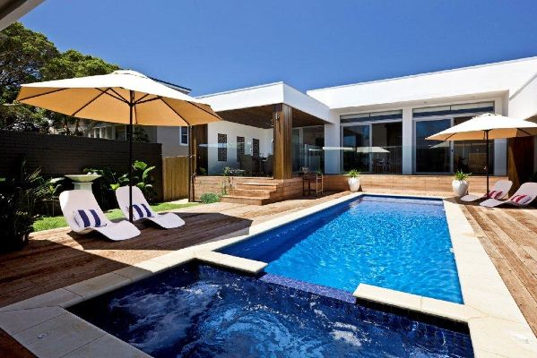 Dark blue pool and spa in Sorrento surrounded by sandstone and pool timbre decking designed and built by Albatross Pools
