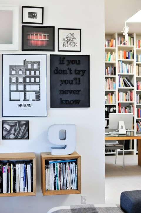 BLIKKFANG: En samling ulike bilder er gruppert sammen på en vegg i stuehjørnet. I bakgrunnen skimtes kontorhjørnet med bokhyller fra gulv til tak.