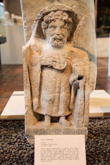 Stèle funéraire (3) Calcaire, provenant de Crain dans l'Yonne. Homme debout, barbu, vêtu a la gauloise d'une tunique et d'un manteau. Il tient une patère remplie de fruits, qui peut évoquer le repas funéraire, et un vase d'où l'eau s'écoule. La tête est disproportionnée est est plus soignée. L'inscription indique une dédicace a la déesse Minerve.