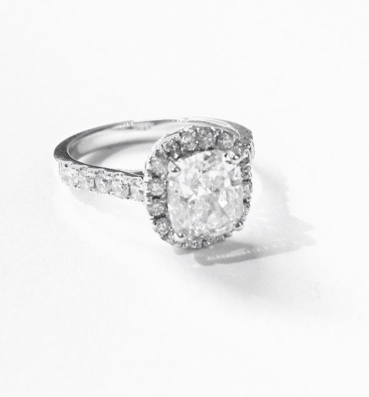 Ring.  Cushion cut centre diamond, pavee halo, white gold. Made by Jenny Greco
