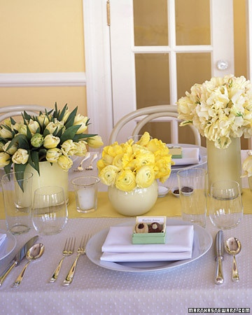 Glass containers, hand-painted on the inside by us, hold flower clusters arranged along a butter-yellow table runner of wide grosgrain ribbon (from left): Dutch tulips, ranunculuses, parrot tulips and sweet peas, and more Dutch tulips. Stems are clipped short so guests can see one another. Tulip-shaped chocolates (by Droste) are on each plate.