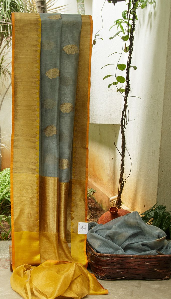 THE CLASSY GREY BENARES LINEN SAREE IS WOVEN WITH GOLDEN ZARI MOTIFS. THE GOLD ZARI WOVEN ON THE MUSTARD PALLU AND BORDER ENHANCE THE LOOK OF THE SARI.