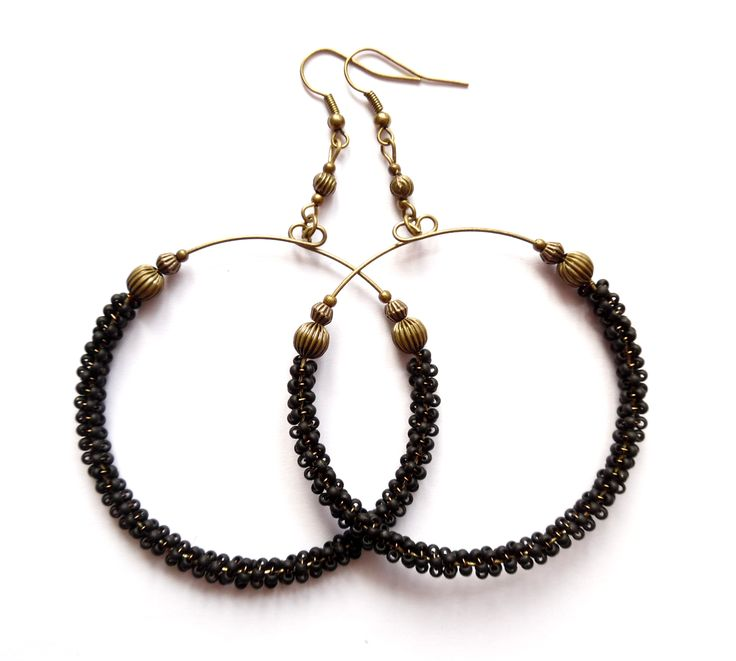 Örhängen med stora ringar i brons och svarta pärlor av glas.  Längd: 9cm