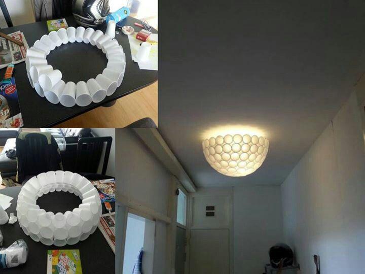 Mooie lamp van plastic bekers aan elkaar gelijmd. Opgehangen dmv ijzeren kruis