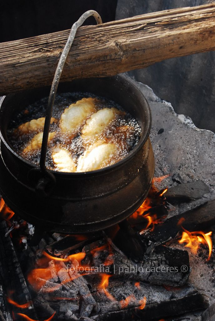Empanadas camperas Comida típica argentina: empanadas fritas en grasa, en olla de hierro al fuego. Una postal criolla.