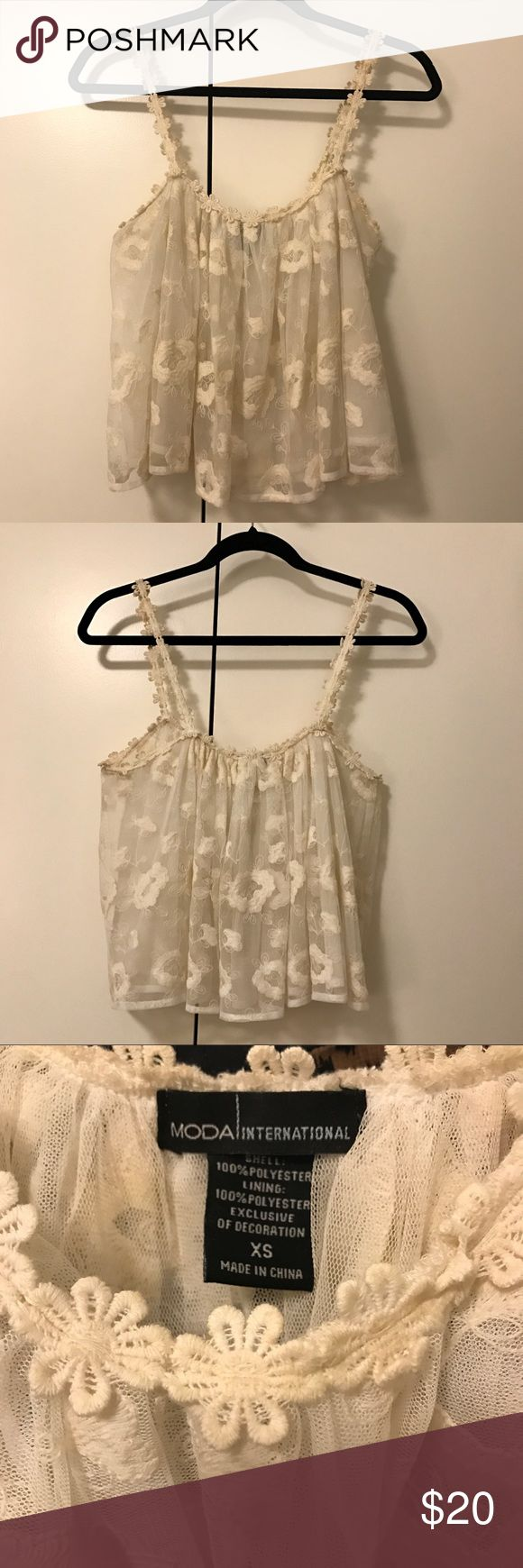 Laced Cream Cropped Top - Moda Internacional Laced cropped top with double lining. Meshed lace and little flower appliqué on the straps. Perfect for a summer day with high waited jeans or shorts. Super dainty and fashionable. Moda International Tops Crop Tops