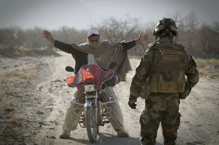 A Hungarian legionnaire from the French Foreign Legion stops an Afghan man on a motorcyle near Tagab in Kapisa province on Jan. 25. The French Foreign Legion, a military unit established in 1831, was created for foreign nationals of any nationality wishing to serve in the French armed forces.