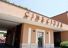 Cinecittà - Wikipedia, la enciclopedia libre  es un gran estudio de cine en Roma que se considera el centro de cine italiano . Los estudios fueron construidos durante la era fascista , como parte de un plan para reactivar la industria del cine italiano. En la década de 1950, el número de producciones internacionales que se están realizando allí llevó a Roma era doblada Hollywood sobre el Tíber .