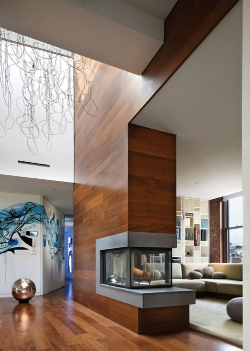 """12 Fabulous Fireplaces: The fireplace in this 3,200 sq ft eco-friendly penthouse called """"Blesso Loft,"""" designed by New York City architect Joel Sanders effectively divides the entry from the living room."""