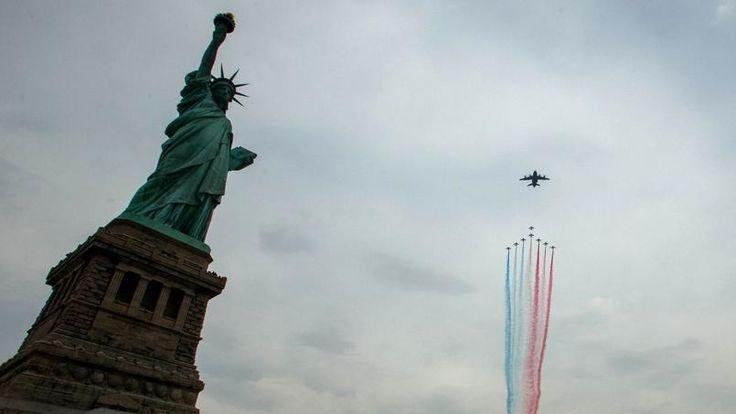 Sous un soleil voilé, huit appareils Alphajet de la légendaire patrouille, redécorés en hommage aux couleurs américaines et emmenés par un avion de transport militaire A400-M, ont survolé à deux reprises, à bonne altitude, l'icônique symbole des Etats-Unis, première étape d'une tournée américaine d'un mois et demi.