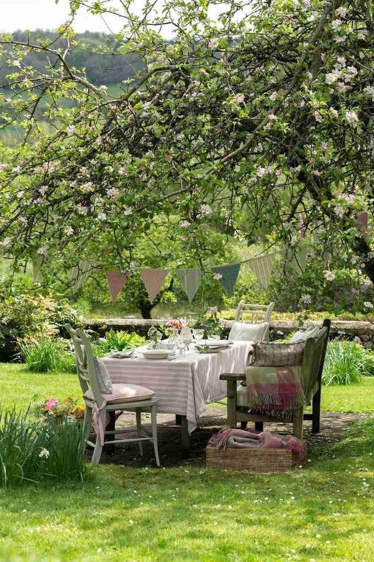 coin repas dans le jardin, aménagé avec des chaises en bois, des textiles de style campagne et une guirlande en fanions