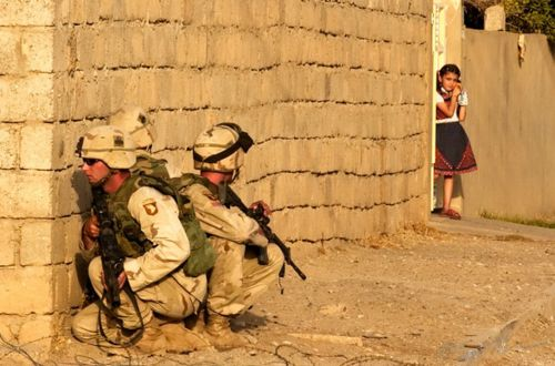 Proud to have served with this unit during this mission!--A local Iraqi girl watches from the doorway of her home as U.S. Army 101st Airborne troops take cover July 23, 2003 near the site where they killed both Uday and Qusay Hussein in Mosul, Iraq the day before. The two sons of the former Iraqi leader Saddam Hussein were cornered in an affluent home in the northern city of Mosul and killed in what U.S. military officials described as a fierce firefight that lasted for several hours.