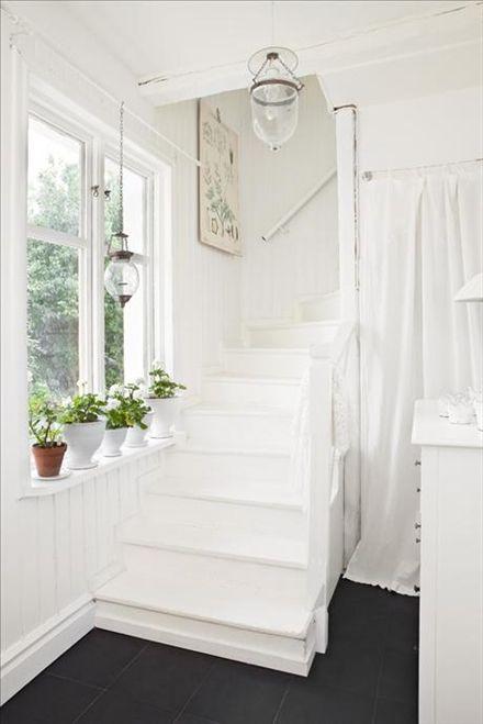 Trappan upp från hallen. Allt är vitmålat med skifferliknande golvklinker som fin kontrast.