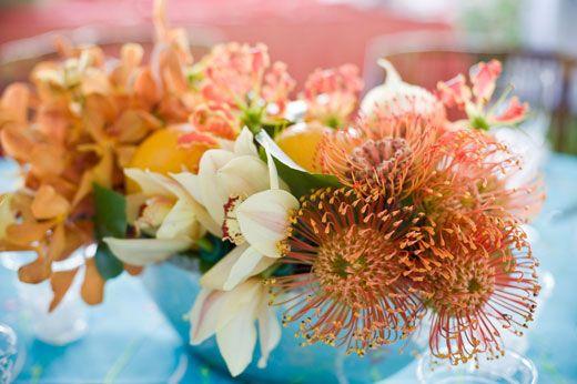 Arrangement of orange mokara orchids, pin cushion, orchids, gloriosa lily and oranges.