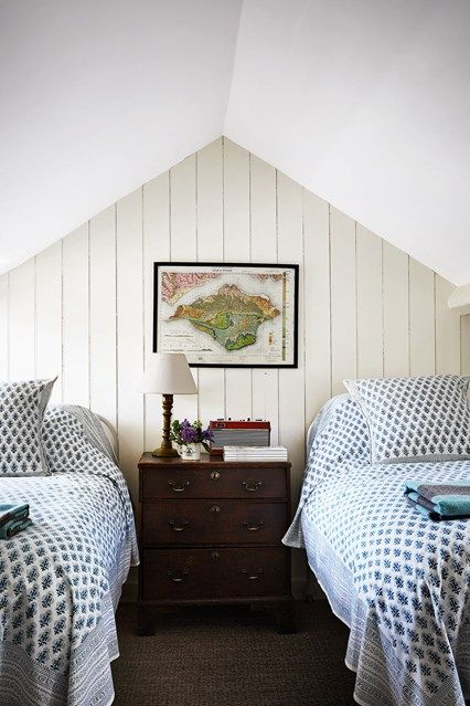 The Attic Bedroom in Georgian Country House. Attic bedroom with wooden panelling and twin beds.