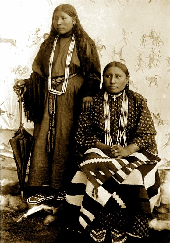 Sioux women called Few Tails, pose in front of a painted Lakota-style war record, Pine Ridge Agency, South Dakota. Photo: ca. 1891.