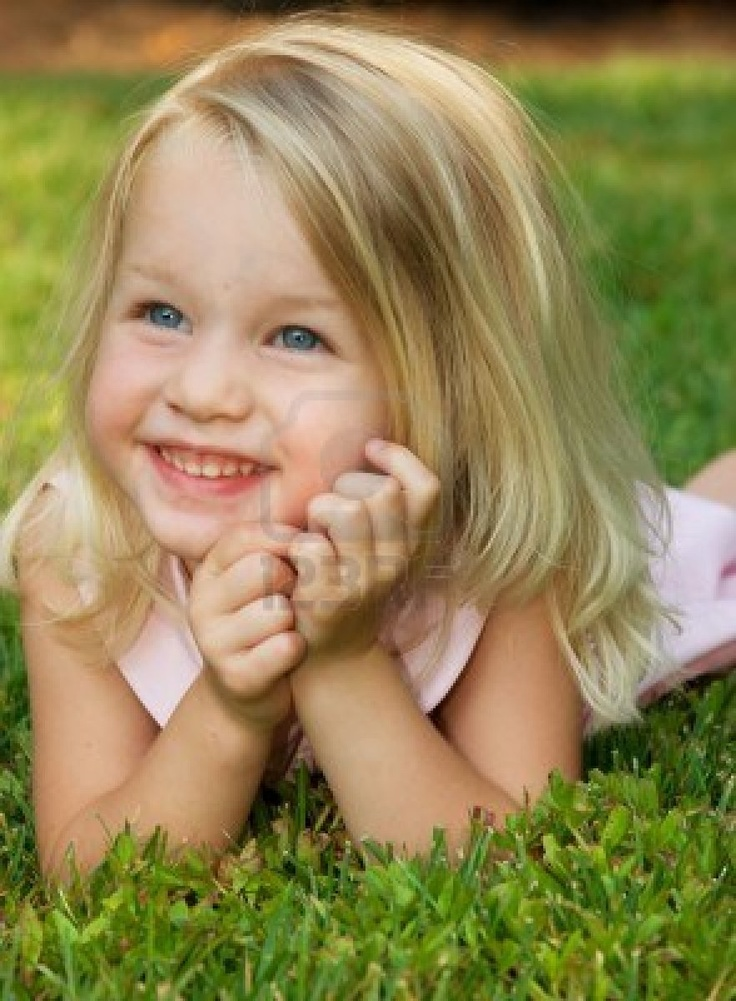 Toddler girl smiling laying on grass, pretty girl Stock Photo