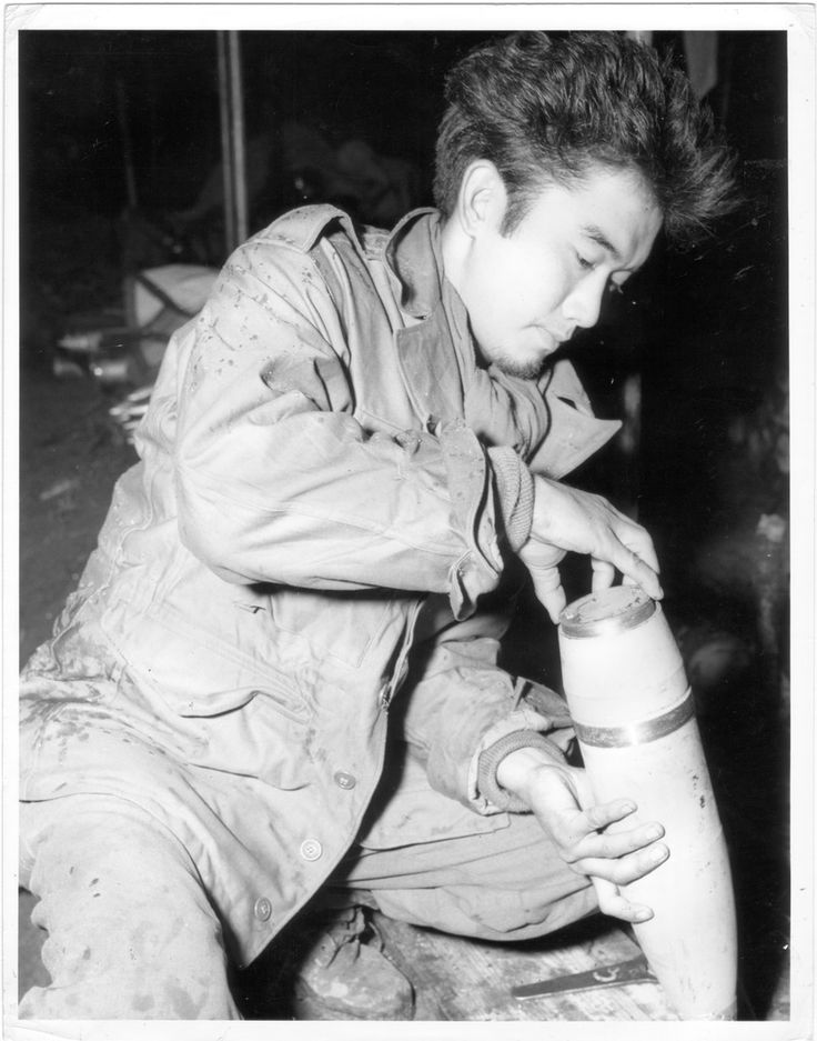 Original caption: A Japanese soldier of the 7th Army, Battery A, 522nd FA, 442nd Combat Team in France, fits base plate to a 105 mm. shell after propaganda pamphlets have been inserted. A small charge of powder in the projectile blows off base plate over enemy territory, allowing leaflets to drift to ground troops below.