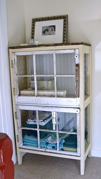 Cabinet constructed of two salvaged windows (the doors), electric knobs as handles (from knob & tube wiring), salvaged wood for the frame, old barn wood for the top, beadboard left over from a wall project as the back, and chicken wire sides #recycle #salvage