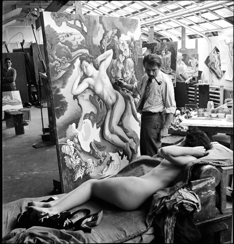 """The American painter Thomas Hart Benton (1889 - 1975) works on his painting """"Persephone"""" (also known as """"The Rape of Persephone"""") in his classroom-studio at the Kansas City Art Institute, Kansas City, Missouri, in 1939. His model is one of his students; other students nearby also paint from the same model."""