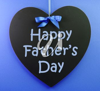 Happy Fathers Day message written on a black blackboard with blue ribbon against a blue background.