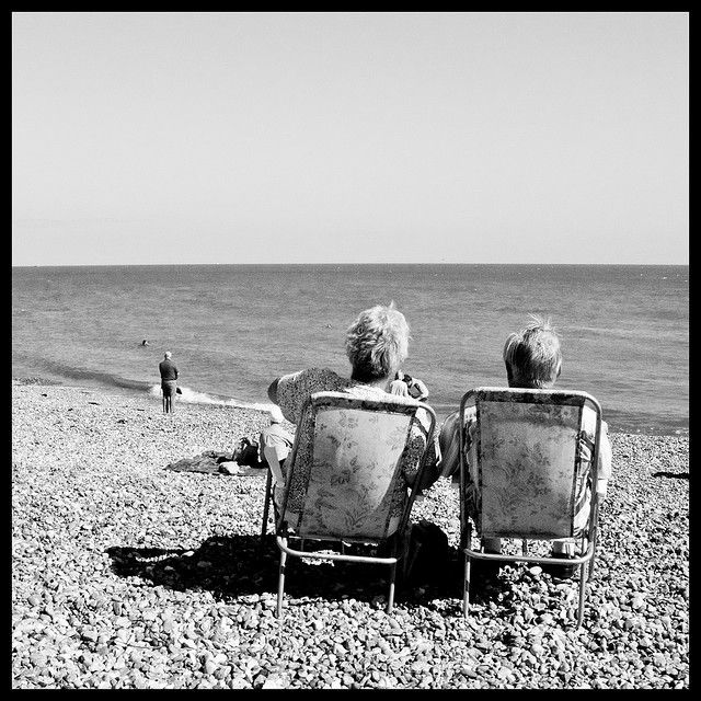 Elderly couple sitting in deck chairs - Eastbourne by samcadby.
