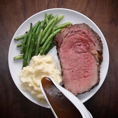 PRIME RIB WITH GARLIC HERB BUTTER Servings: 7-9  INGREDIENTS 1 cup butter, softened 7 cloves garlic, minced 2 tablespoons fresh rosemary, finely chopped 2 tablespoons fresh thyme, finely chopped 2 tablespoons salt 1 tablespoon pepper 5-7 pound boneless ribeye roast, trimmed 2 tablespoons flour 2 cups beef stock Mashed potatoes, to serve Green beans, to serve  PREPARATION Preheat oven to 500°F/260°C. Mix together the butter, garlic, herbs, salt, and pepper in a bowl until evenly combined. Rub…