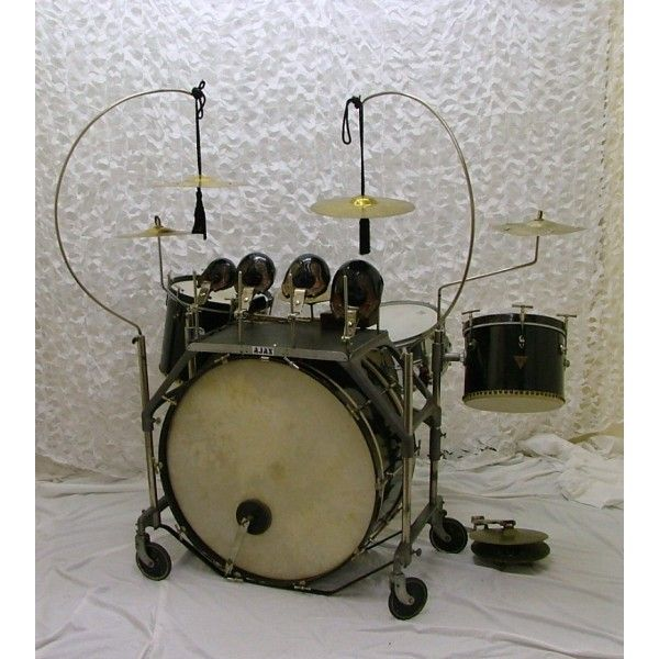 1937 Ajax 'triangle badge' drum kit, black. Mounted in original console on 4 wheels, 2 with brakes. Snare basket mounted off console; 2 z cymbal arms, 2 swan neck cymbal arms.