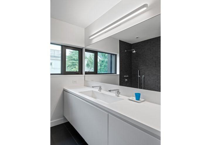 Geometrie nette e stile contemporaneo anche in bagno, dove domina il bianco dei mobili su misura. Le finestre affacciano sul verde del giardino