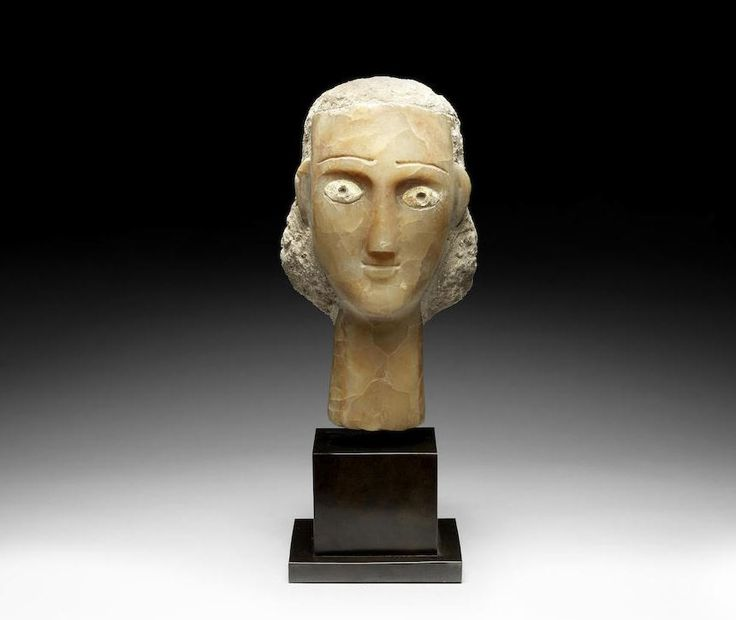 South Arabian calcite female head,  1st century B.C. - 1st century A.D. Her hair modelled in plaster with slight traces of over-painted black pigment at the back, the eyes inlaid with shell, the curved brows recessed for inlays, now missing, with long slender nose and elongated neck, 25.5 cm high. Private collection