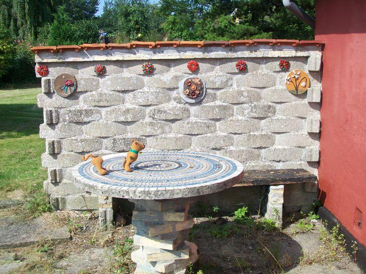 Vores hus er flere steder prydet med murede ting og mosaik. Her: Mosaik bord og bænk på terrassen ved gildesalen.