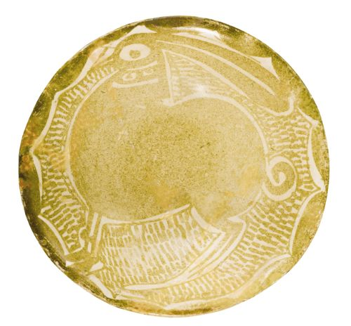 An Abbasid lustre dish featuring a hare, Iraq, 9th/10th century the earthenware body painted in a golden lustre on an opaque white glaze, depicting a plump hare on a hatched line ground within a scalloped border 12.7cm. diam. 5.1cm. height.