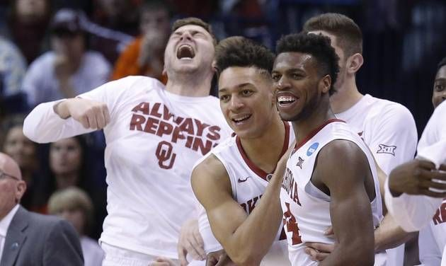 Oklahoma guard Buddy Hield, right, celebrates with teammate Jamuni McNeace, center, in the first half of a second-round men's college basketball game against VCU in the NCAA Tournament Sunday, March 20, 2016, in Oklahoma City. (AP Photo/Sue Ogrocki)