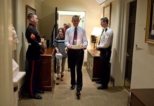 """Dec. 2, 2013 """"Joined by Chief of Staff Denis McDonough's daughter, the President carries a birthday cake to surprise McDonough in his West Wing office.""""  (Official White House Photo by Pete Souza)"""