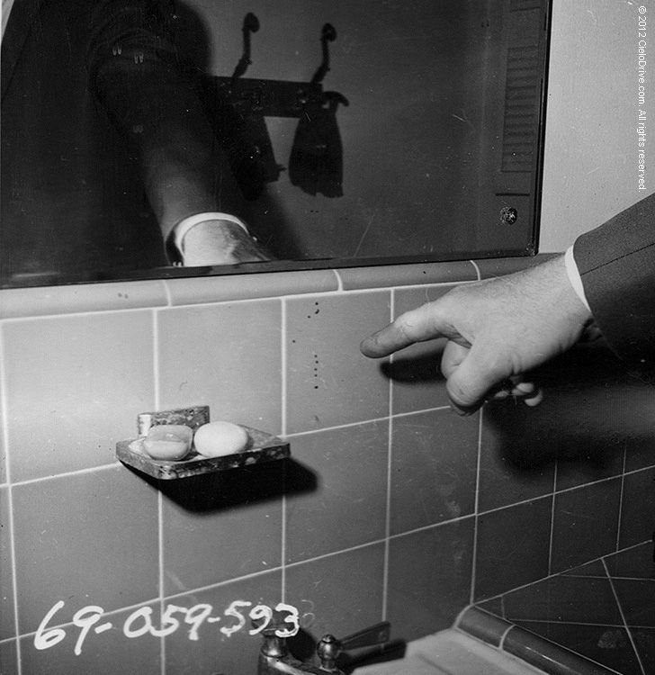 An officer points to blood left on the wall of one of the bathrooms at 10050 Cielo Drive.