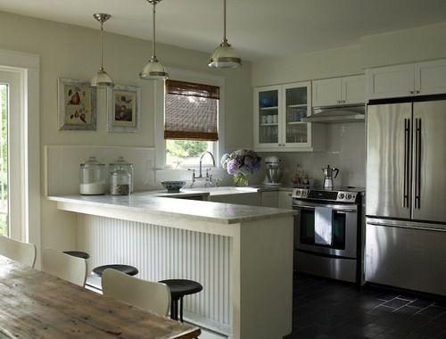 Beautiful cottage kitchen design with creamy white shaker kitchen cabinets, peninsula, honed marble counter tops, beadboard kitchen peninsula designs