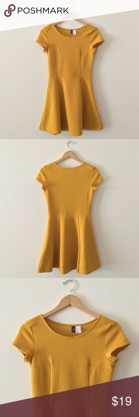 """H&M Mustard Dress Short sleeve mustard colored dress with textured pattern. Skirt flares out at waist. Excellent used condition. US 6 is a size medium. Length: 32.5"""" Armpit to Armpit: 16.5"""" H&M Dresses"""
