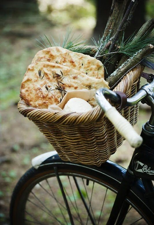 Fougasse, a flat bread usually associated with Provence, usually made with herbs, black olives, sometimes sun-dried tomatoes..Also in the bike basket is goat cheese.