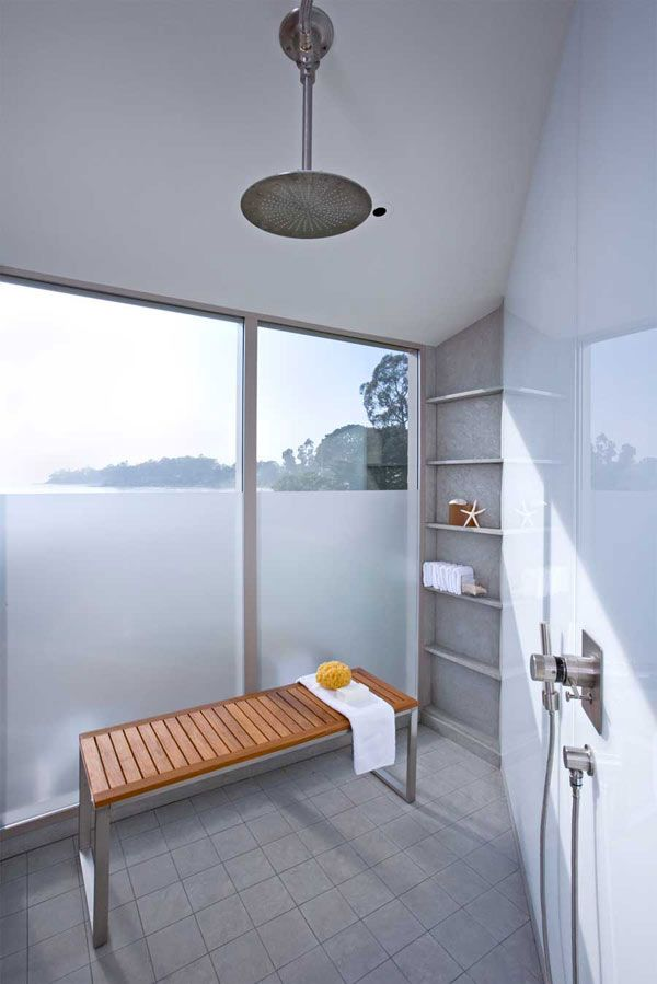 floor to ceiling windows in huge shower with bench and plenty of shelves for toiletries