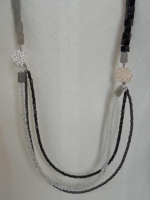 Lange ketting met aan de ene kant rechthoekjes van labradoriet en aan de andere kant kubusjes van zwarte onyx. Bovenaan twee druppels van witte agaat en een stukje sterling zilveren ketting. Onderaan een rijtje zwarte spinel, een rijtje bergkristal en een rijtje hematiet. De bloemetjes zijn sterling zilver.  190 euro