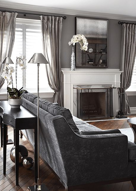 Gray living room. Charcoal sofa with curved armrests in microsuede, curved black wood condole table with drawers, polished chrome floor lamps, fireplace with an off-white mantel with marble insert, taffeta silk striped drapes, black iron forged curtain rod, antique finished distressed mirror, gray walls, solid wood under oil flooring, white traditional trim work.