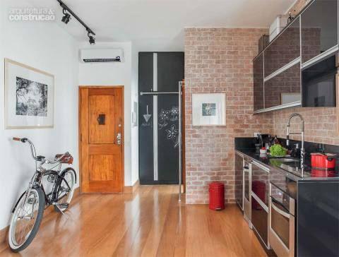 A cozinha se resume à bancada de 2,50 m de comprimento, suficiente para encaixar cooktop, cuba e área de trabalho. No armário da despensa (ao fundo), as portas forradas de laminado do tipo lousa são usadas para anotar recados e listas de compras. Projeto Escala Arquitetura e André Passini.