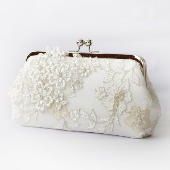 The bridal bag is made of heavy ivory satin and wrapped around with a layer of embroidered tulle lace and adorned with an silver thread embroidered Alencon lace appliqué of sakura / cherry blossom flowers and branches. Clutch bag can be mounted on a silver tone or a light rose gold tone kiss lock purse frame.It is perfect gift for her at all occasions -- weddings, bridal shower, to bridesmaids, to mother of bride or groom and beloved ones. Clutch detail details of this listing: Base Fabr...