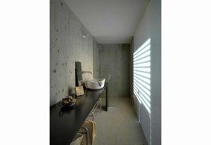 Nei bagni di House Y le pareti sono in cemento a vista, la rubinetteria in acciaio satinato e i lavabi in pietra. I contrasti materici sono il fil rouge del progetto di FL Architetti. Foto di: P. L. Architetti
