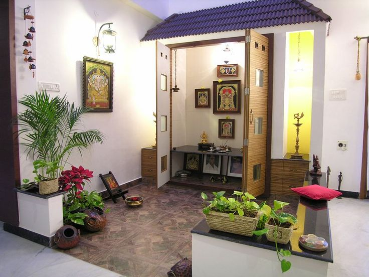 Puja area in the corner is decorated with traditional artefacts and green planters which brighten up the space.